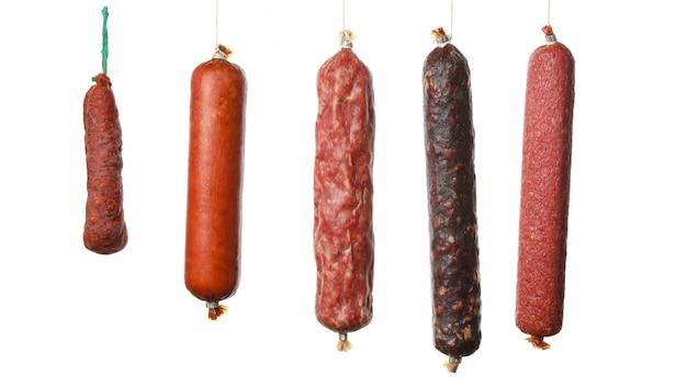 Différentes saucisses suspendues isolés sur blanc