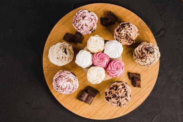 Différentes saveurs de cupcakes et de crèmes fouettées sur un support en bois