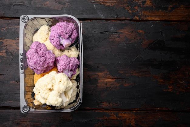 Différentes sortes de chou-fleur. ensemble violet, jaune et blanc, dans un conteneur, sur un vieux fond de table en bois foncé, vue de dessus à plat, avec espace de copie pour le texte