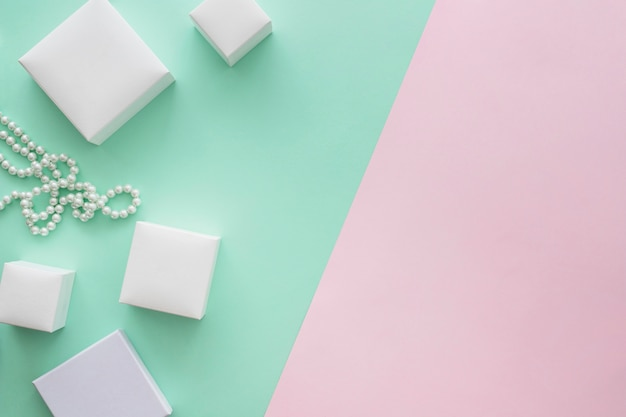 Différentes tailles de boîtes et collier de perles sur fond coloré