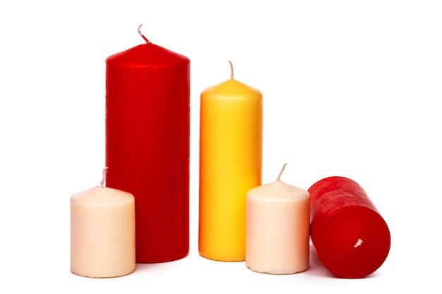 Différentes tailles et couleurs de bougies isolées sur un blanc