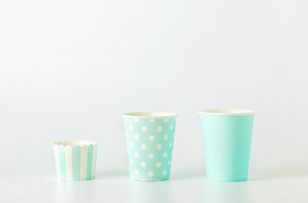 Différentes tailles de gobelet en papier bleu à pois blancs et à rayures sur fond blanc