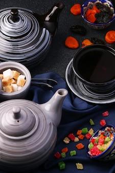 Différentes théières et bonbons. divers thé et théière avec différents sucres sur table sombre