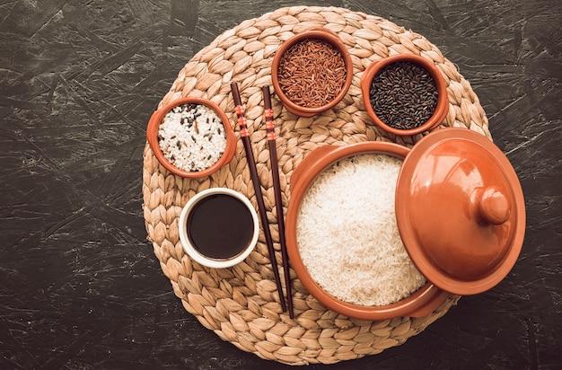 Différentes variétés de grains de riz non cuites sur un bol avec une sauce soja sur le napperon