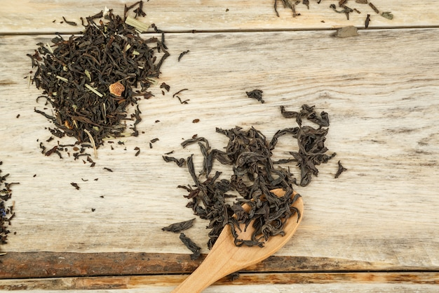 Différentes variétés de thé naturel sur une cuillère en bambou sur un fond en bois