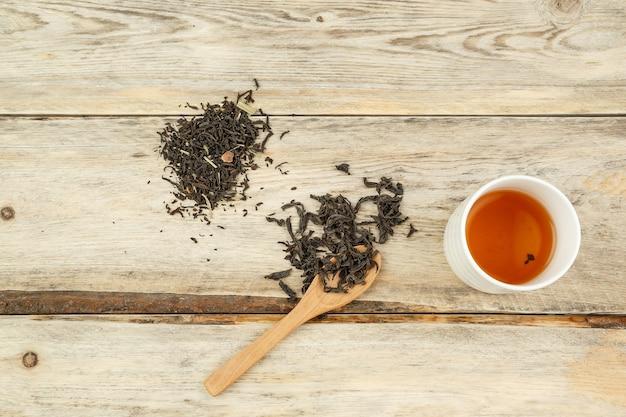 Différentes variétés de thé naturel sur une cuillère et brassées dans un verre sur un fond en bois.