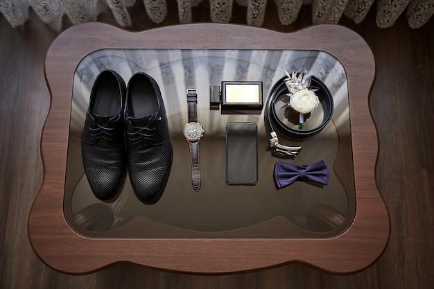 Différents accessoires d'un homme d'affaires pour créer le style d'un peuple se trouvent sur une surface en bois