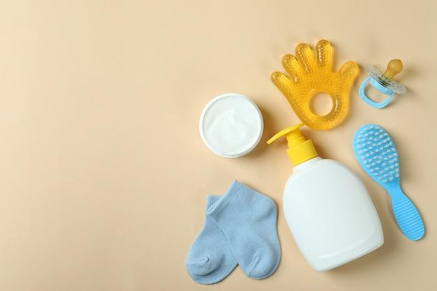 Différents accessoires d'hygiène bébé sur fond beige