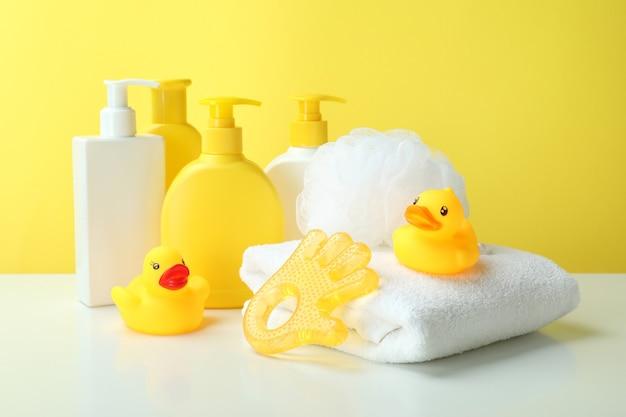 Différents accessoires d'hygiène pour bébé sur fond jaune