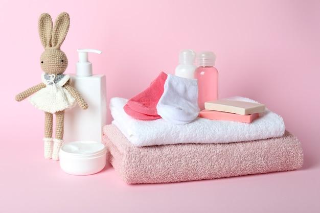 Différents accessoires d'hygiène pour bébé sur fond rose