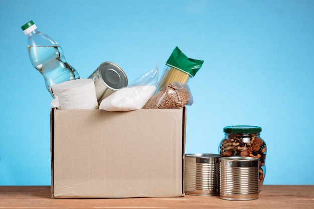 Différents aliments dans une boîte de bénévoles. faire un don box, don et concept de charité. boîte de dons de nourriture sur fond bleu.