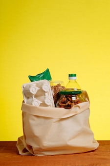 Différents aliments dans un sac en papier sur table en bois, sur fond jaune