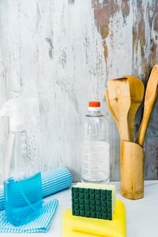 Différents articles de nettoyage ménagers sur un comptoir en marbre dans une cuisine