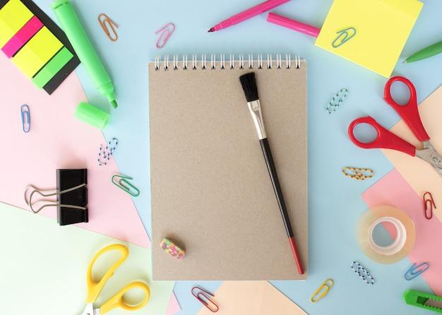 Différents articles de papeterie sur fond coloré multicolore à plat avec un espace pour le texte de retour à l'école