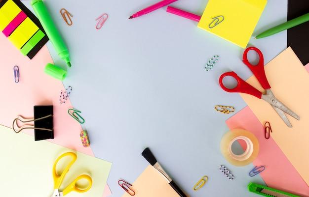 Différents articles de papeterie sur fond coloré multicolore à plat avec un espace pour le texte de retour à l'école...