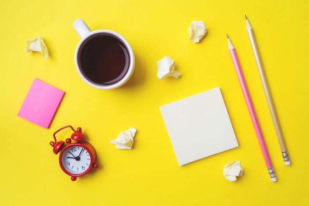 Différents articles de papeterie, une tasse de café et une horloge