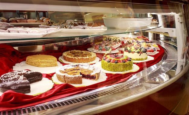 Différents beaux gâteaux colorés savoureux sur une vitrine au café