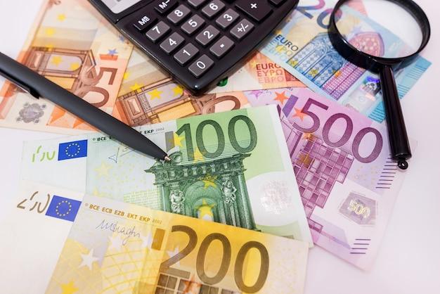 Différents billets en euros, calculatrice, loupe et stylo. notion financière.