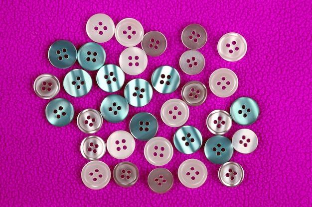 Différents boutons de nacre sur un tissu rose. vêtements & accessoires