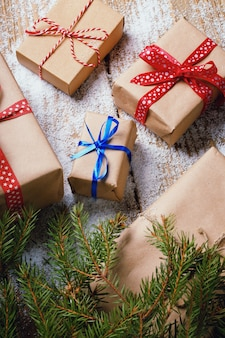 Différents cadeaux du nouvel an emballés dans du papier d'emballage sous la branche d'arbre de noël