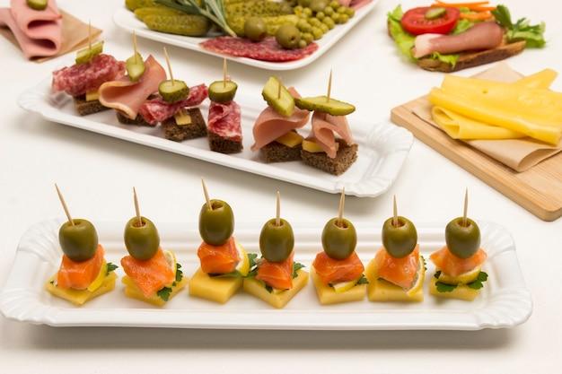 Différents canapés au saumon, concombre, tomates, fromage, viande sur fond blanc
