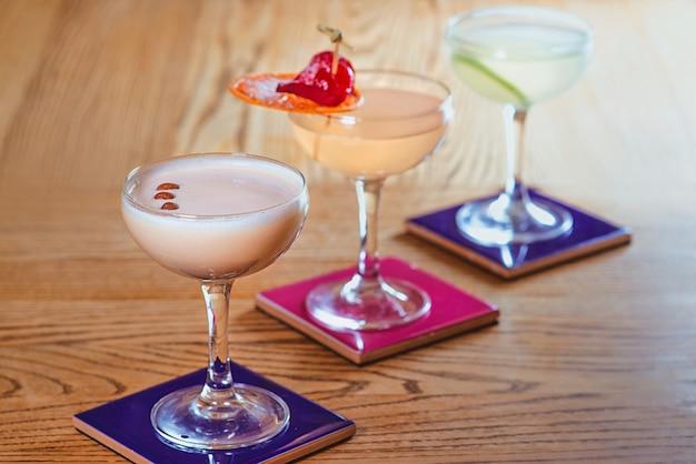 Différents cocktails colorés avec alcool et sans alcool dans les verres sur la table