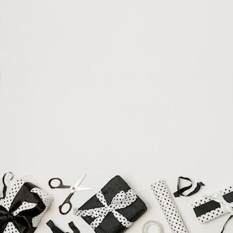 Différents coffrets cadeaux emballés noirs et blancs avec des ciseaux et du papier de design