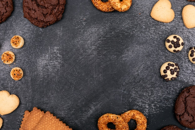 Différents cookies vue de dessus sur une surface sombre avec copie espace