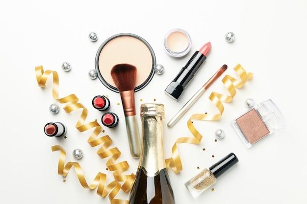 Différents cosmétiques de maquillage et champagne sur fond blanc. accessoires femmes