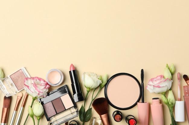 Différents cosmétiques de maquillage et fleurs sur fond beige. accessoires femmes