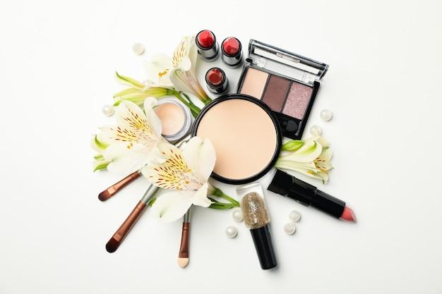 Différents cosmétiques de maquillage et fleurs sur fond blanc. accessoires femmes