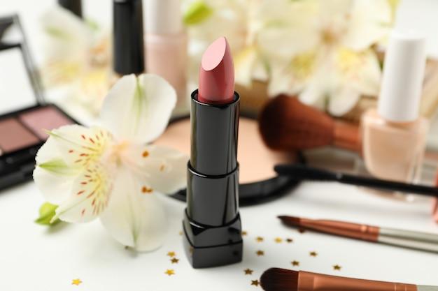 Différents cosmétiques de maquillage et fleurs sur fond blanc