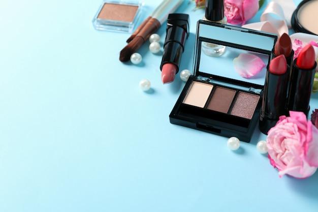Différents cosmétiques de maquillage et fleurs sur fond bleu. accessoires femmes