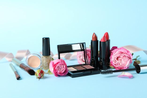 Différents cosmétiques de maquillage et fleurs sur fond bleu