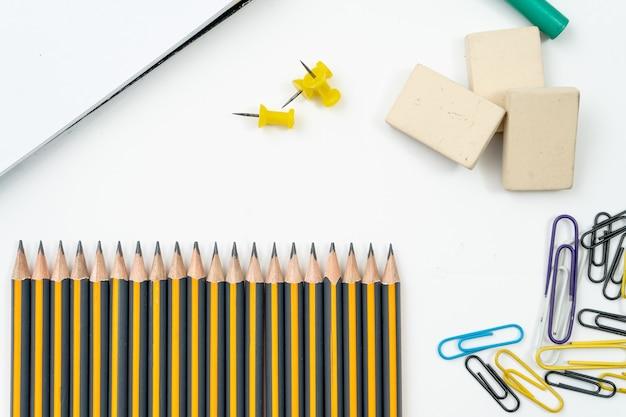 Différents éléments ou fournitures scolaires indispensables tels que crayons gommes et stylo à encre