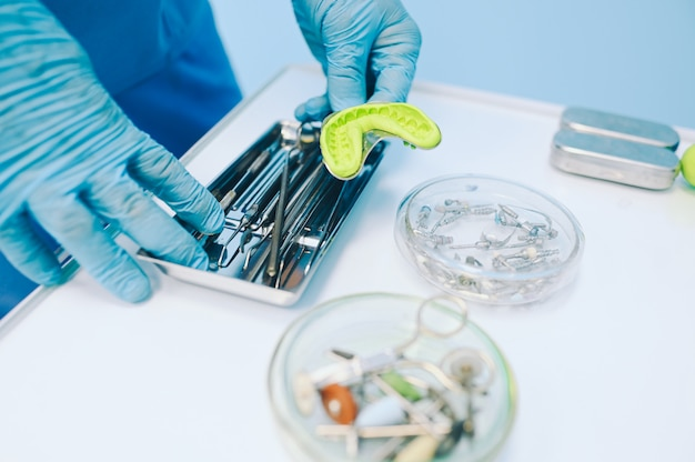 Différents équipements dentaires professionnels, instruments et outils dans une clinique de bureau de stomatologie de dentistes sur fond blanc. moulage en silicone de la mâchoire.