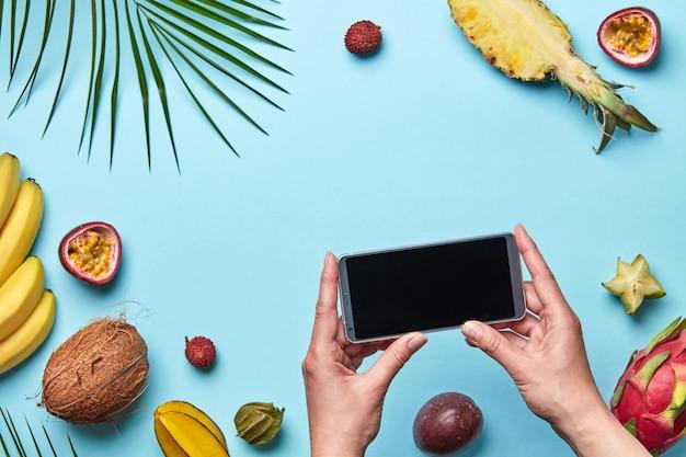 Différents fruits exotiques et une feuille de palmier avec téléphone portable