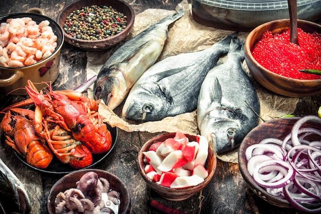 Différents fruits de mer aux crevettes et caviar rouge. sur un fond en bois.
