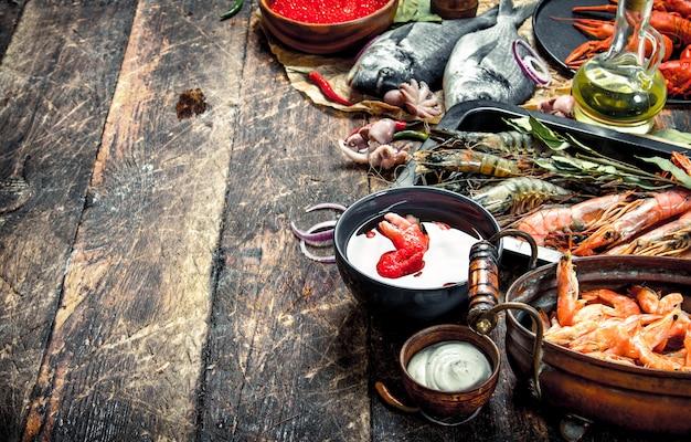 Différents fruits de mer aux crevettes et caviar rouge sur une table en bois.