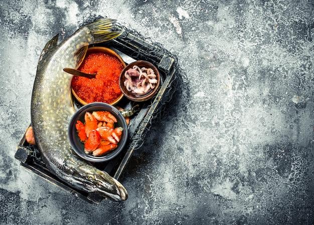 Différents fruits de mer dans la boîte. sur un fond rustique.