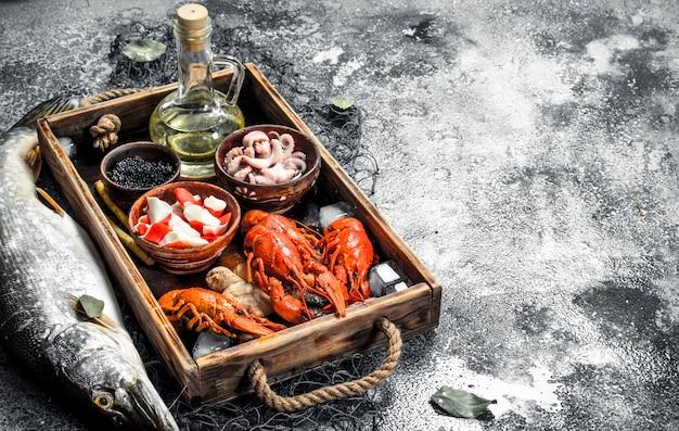 Différents fruits de mer sur un plateau en bois. sur un fond rustique.
