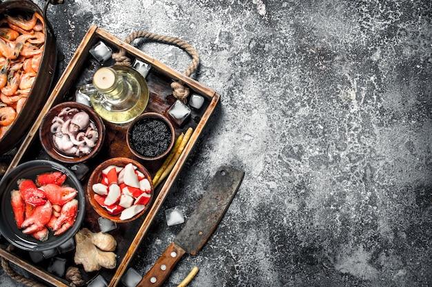 Différents fruits de mer sur un plateau en bois sur une table rustique.
