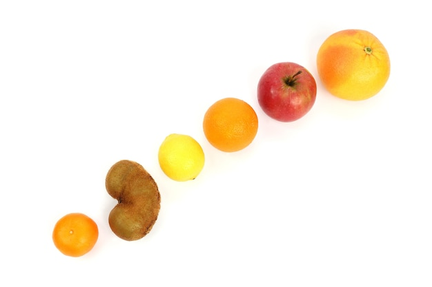 Différents fruits sur une surface en pente sur fond blanc
