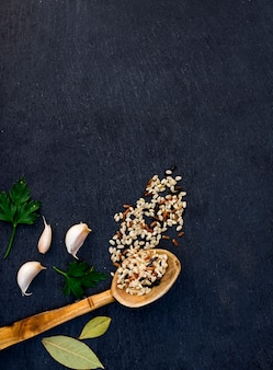 Différents grains de riz dans une cuillère en bois