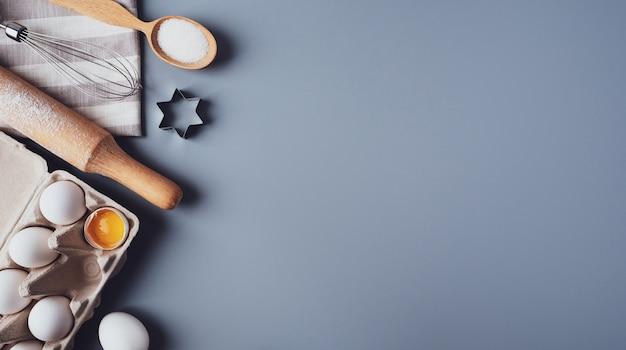 Différents ingrédients et ustensiles de cuisine pour faire des biscuits ou des cupcakes, à plat, copyspace.