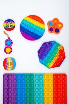 Différents jouets à la mode pop it fidget sur fond blanc jouets colorés en silicone populaires mise à plat