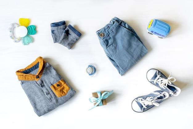 Différents jouets pour enfants, vêtements, accessoires, coffret cadeau sur table blanche avec espace de copie, mise à plat. douche de bébé, décorations, trucs, cadeau pour l'anniversaire de la première année du garçon, fête du nouveau-né.
