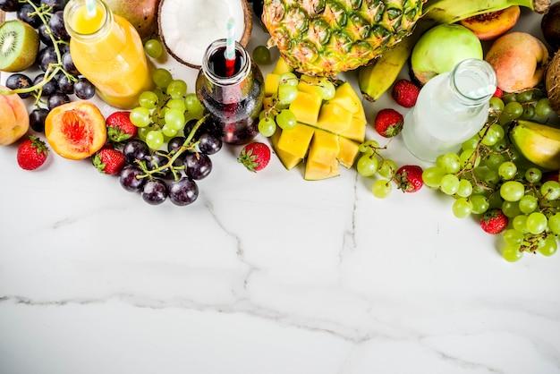 Différents jus de fruits smoothies concept régime de vitamines d'été avec des fruits tropicaux et des baies sur un fond clair