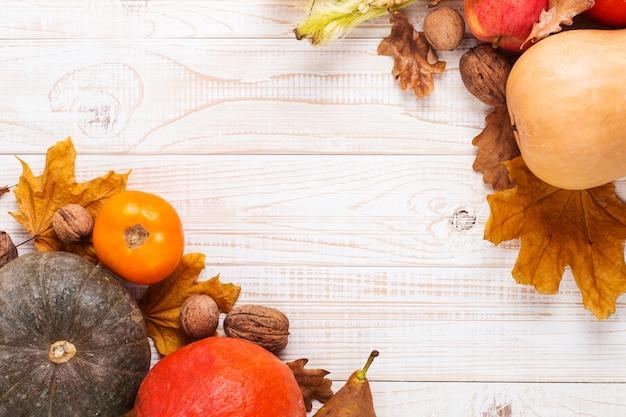 Différents légumes, citrouilles, pommes, poires, noix, tomates et feuilles sèches sur un fond en bois blanc. humeur d'automne, surface. récolte .