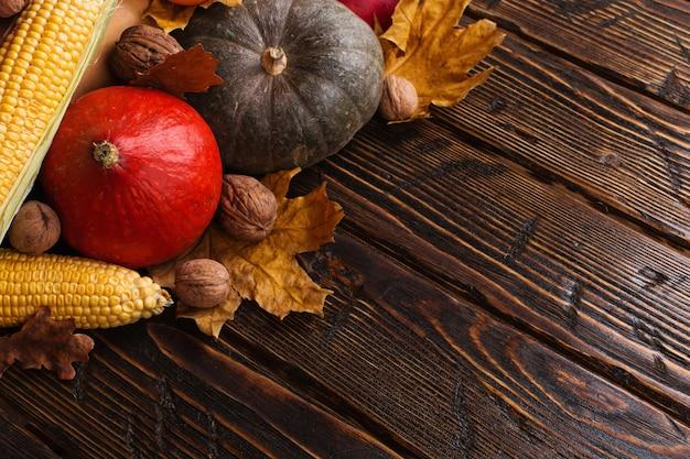 Différents légumes, citrouilles, pommes, poires, noix, tomates, maïs, feuilles jaunes sèches sur fond en bois. humeur d'automne, surface. récolte .
